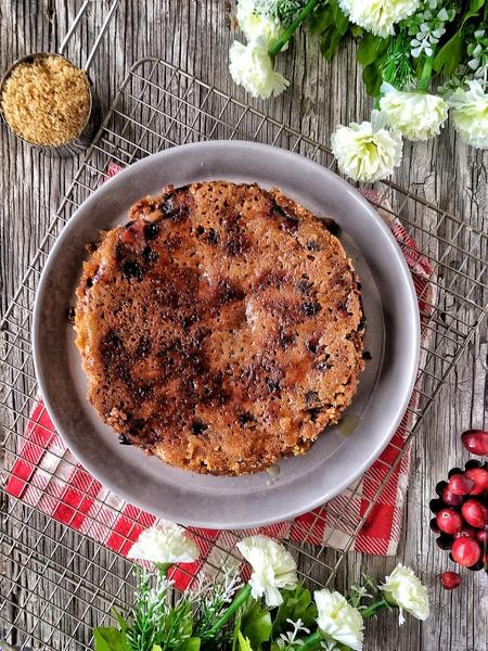 pastel de arándanos rojos sobre mesa de madera con flores blancas